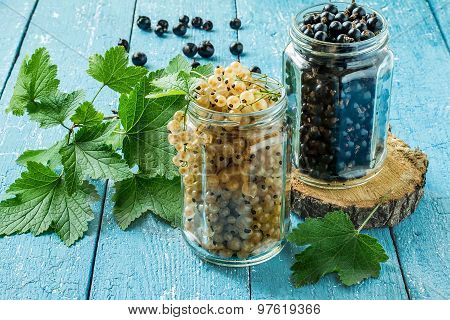 Ripe Black And White Currants In Glass Jars