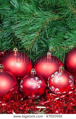 Several Red Christmas Baubles Tinsel And Xmas Tree