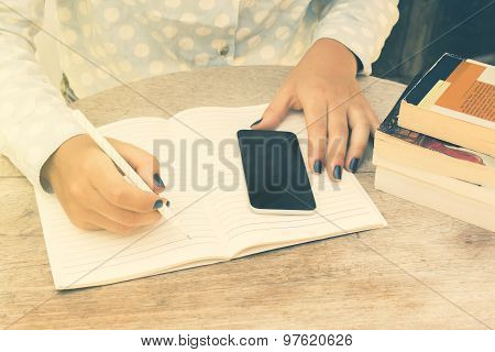 Girl Writes In A Notebook, With Cell Phone And Books