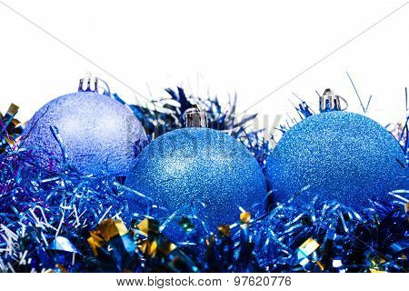 Three Blue Christmas Baubles And Tinsel Isolated