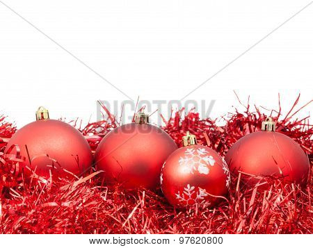 Four Red Christmas Baubles And Tinsel Isolated