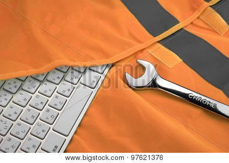 Keyboard In The Orange Reflective Safety Vest And Wrench