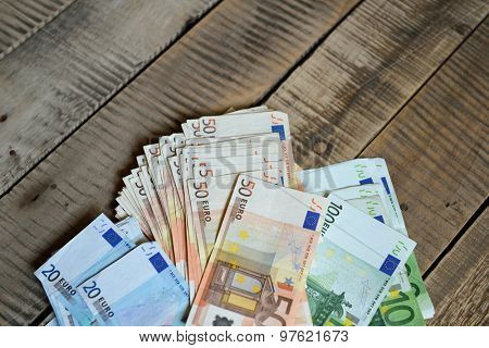 Euro banknotes. Background with european cash money on wooden background.