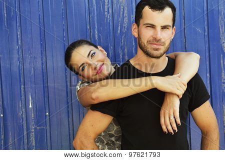 Portrait of young attractive heterosexual couple outdoor over grunge blue background. Beautiful woman embracing your boyfriend, image toned.