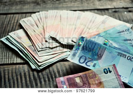 Euro banknotes. Background with european cash money on wooden background. Image toned.