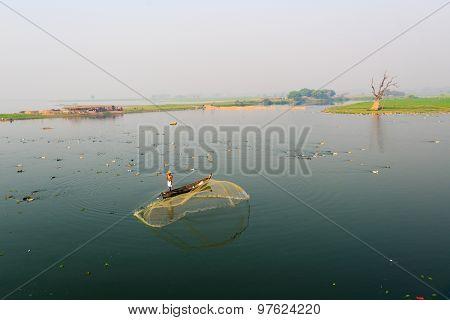 MANDALAY - FEB 28, 2015 : A man throw net for catching fish near U-Bein bridge in Mandalay, Myanmar. The U-Bein bridge is the longest teak bridge in the world