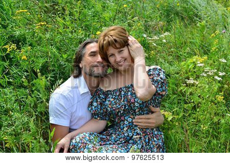 Loving Couple Sitting On The Grass In  Summer