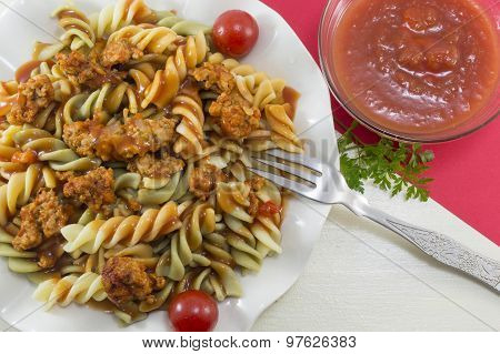 Colored Pasta With Meat Served With A Bowl Of Natural Tomato Sauce