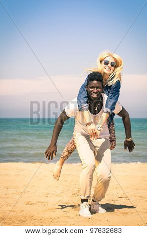 Young Couple Playing At The Beach Having Fun With A Piggyback Jump - Happy Mixed Race Man And Woman