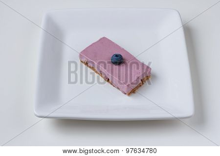 Blueberry cheesecake on a white plate against a white background.