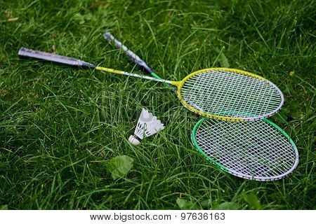 Rackets and shuttlecocks for badminton on the grass.