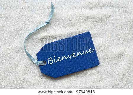 Bienvenue Means Welcome On Blue Label Sand Background