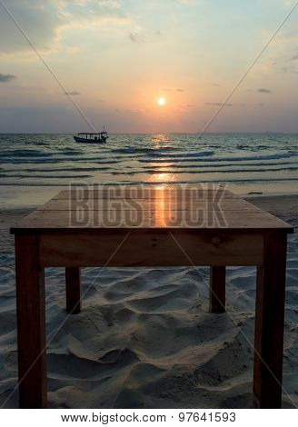 Sun Glade On Top Of Wooden Table At Sunset With Seaview Background