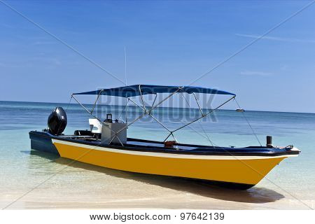Yellow luxury motor boat anchored on a sandy beach on diving and snorkeling tour