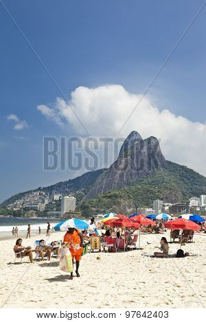 Beach life on Ipanema Rio de Janeiro people relaxing under umbrellas sitting in sun loungers playing
