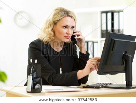 Middle-aged pretty businesswoman working at pc in office