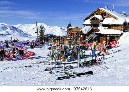 People are relaxing at a chalet bar after skiing and snowboarding in in the 3 Valleys Ski Resort
