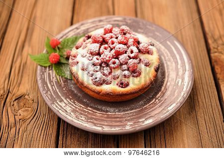 Homemade Tasty Cake With Fresh Wild Raspberries And Leaves Decorated With Icing Sugar In Brown Plate