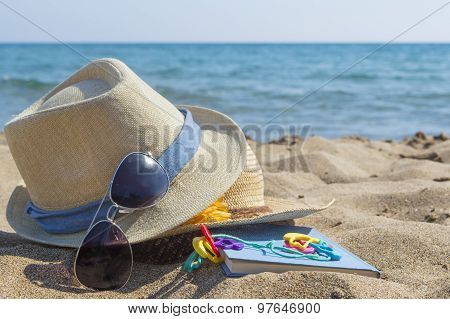 Straw Hats, Sunglasses And A Book On The Beach. Summer Vacation Accessories