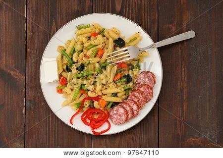 Penne With Green Beans, Red Hot Pepper, Salami And Feta Cheese With Fork In White Plate On Dark Wood