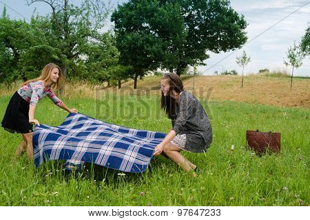 Two girls  spreading a blanket for picnic