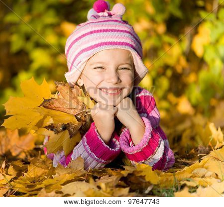 smiling little girl lie on the autumn leaves