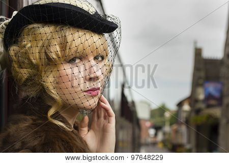 Elegant retro / fifties style woman wearing a veiled black hat
