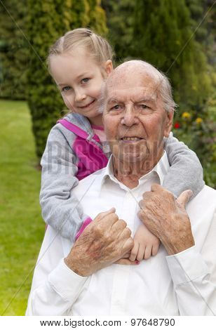 95 years old english man with granddaughter in garden