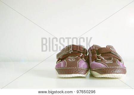 Baby booties on a white wood. Copy space