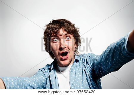Close Up Portrait Of A Young Shocked Man Holding A Smartphone Digital Camera With His Hands And Taki