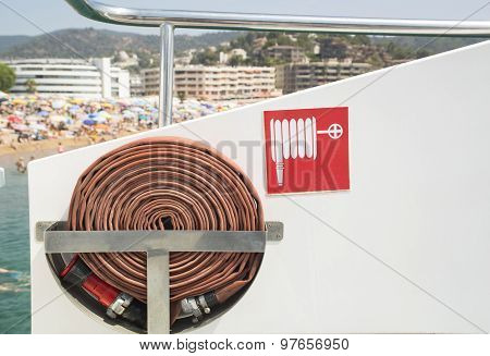 Fire hose and sign on the boat.
