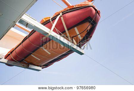 Orange Lifeboat Hanging On Ship At Sea