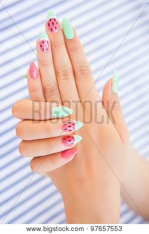 Hands close up of young woman with watermelon manicure summer  nail art  concept