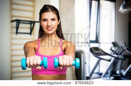 Portrait of a young woman working out in a gym
