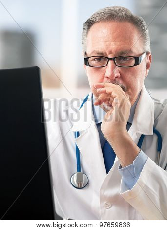 Portrait of a doctor using his computer
