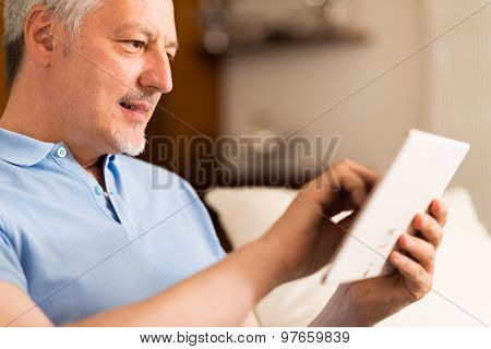 Portrait of a smiling mature man using a digital tablet in his living room