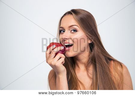 Portrait of a young girl biting apple isolated on a white background