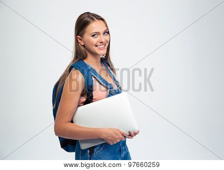 Smiling female student holding laptop and looking at camera isolated on a white background