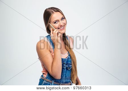 Smiling young girl talking on the phone and looking at camera isolated on a white background