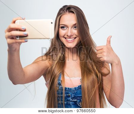 Smiling girl making selfie photo on smartphone and showing thumb up isolated on a white background