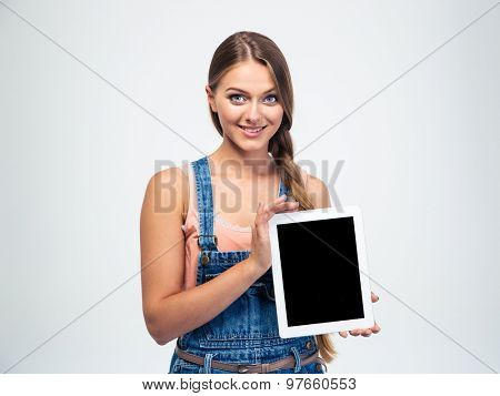 Smiling young woman showing blank tablet computer screen isolated on a white background. Looking at camera