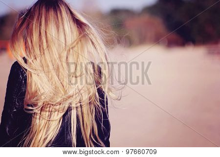 Back view of the young female with beautiful blond straight long hairs in motion