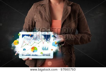Person holding a white touchpad with cloud technology and charts