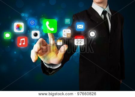 Businessman pressing colorful mobile app icons with bokeh background