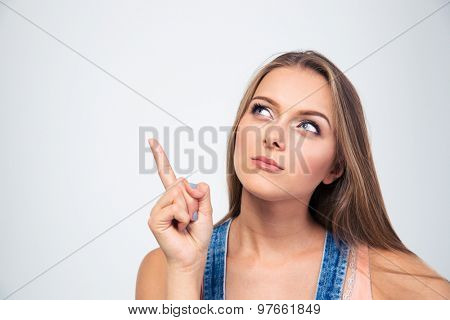Portrait of a pensive young woman looking up at copyspace isolated on a white background