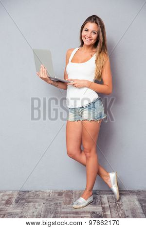 Full length portrait of a happy beautiful girl standing with laptop on gray background. Looking at camera