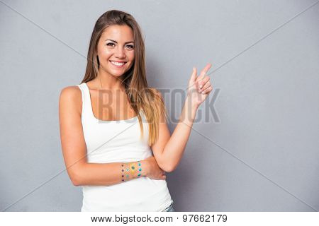 Smiling young girl pointing finger away over gray background. Looking at camera