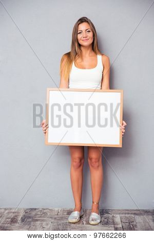 Pretty young girl holding blank board on gray background. Looking at camera