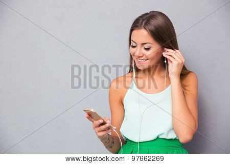 Smiling young girl listening music on smartphone over gray background