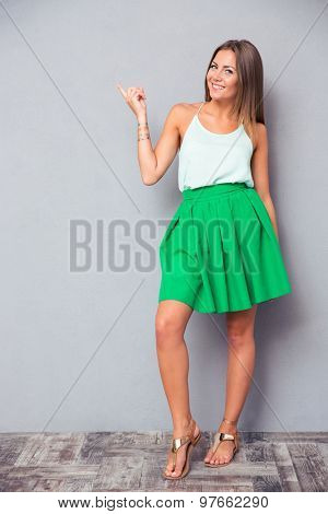 Full length portrait of a happy cute girl pointing finger away and looking at camera over gray background